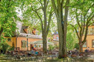 Kastanienhof Altes Pfarrhaus Pforzheim, Außenansicht Bäume, Stühle, Biergarten