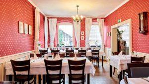 Innenansicht Altes Pfarrhaus Brötzingen, Rote Tapete, Saal mit mehreren Tischen